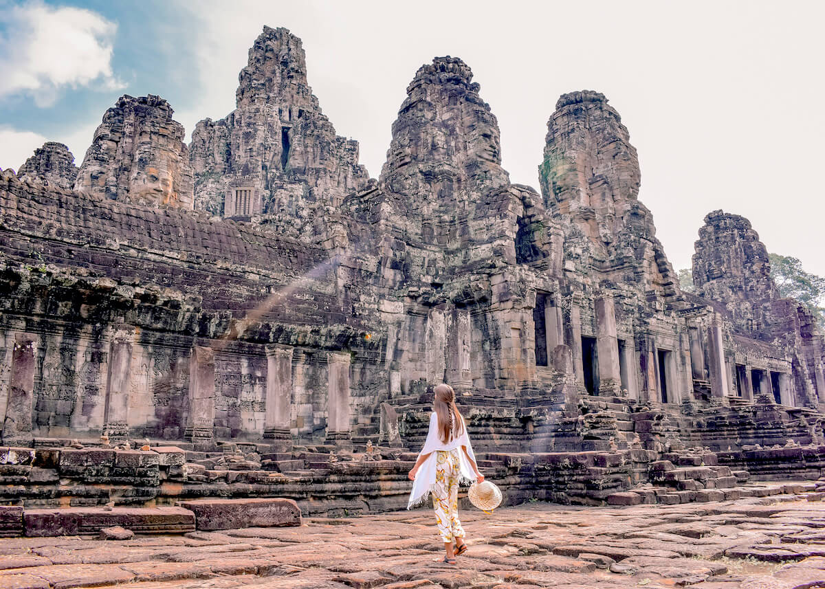girl walking in front of temple ruins in Angkor