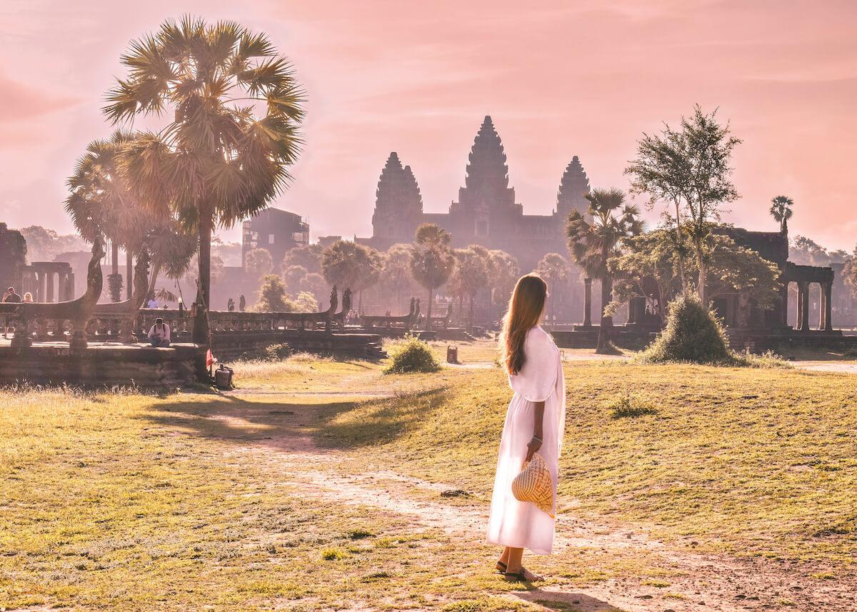 girl watching the sunrise behind Angkor Wat in Cambodia