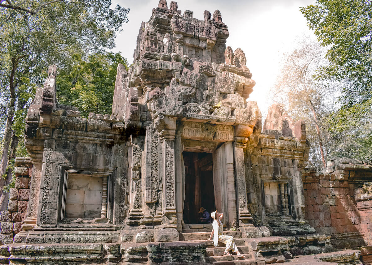 girl sitting in front of temple ruins in Angkor