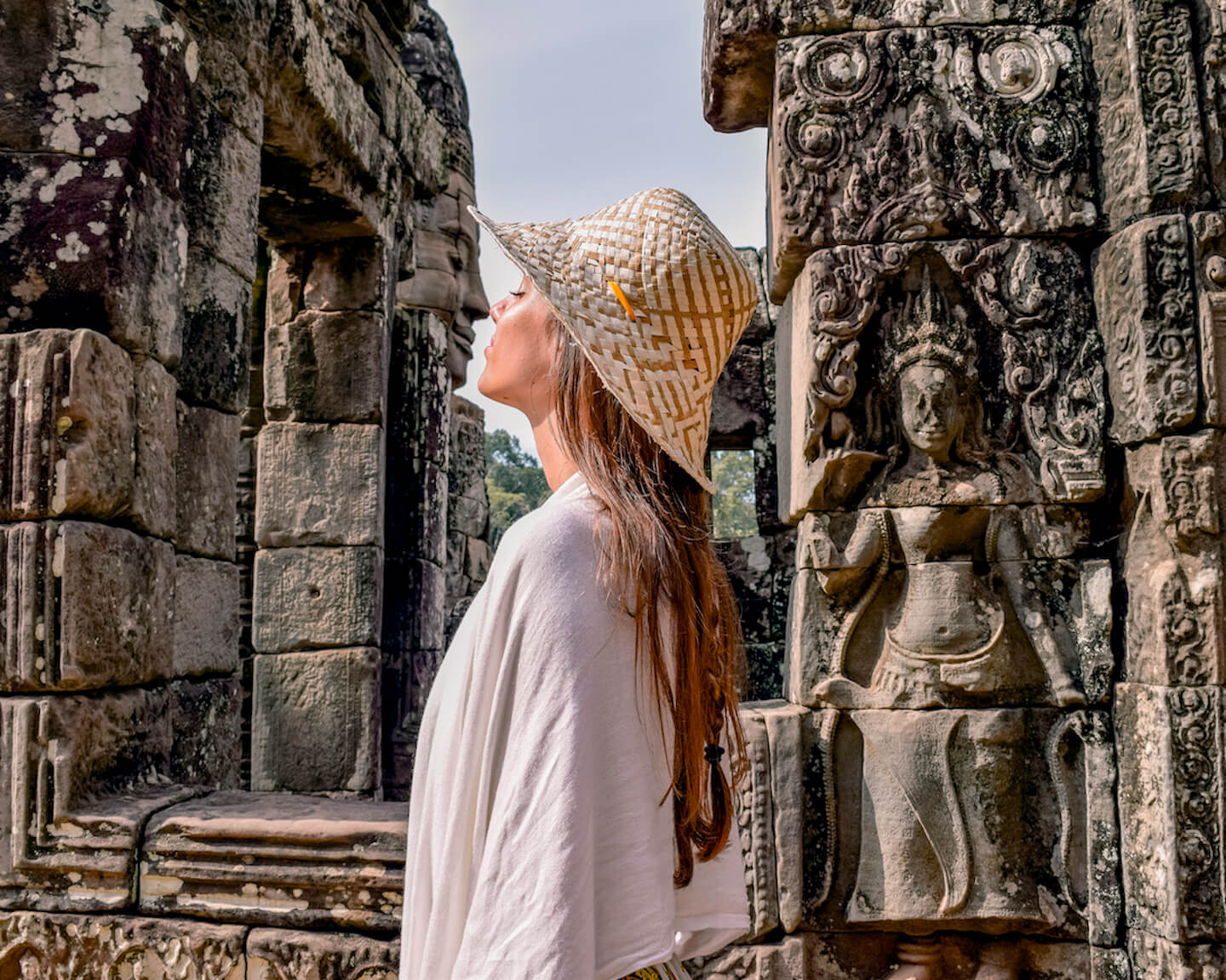 girl pretending to kiss stone face at temple ruins