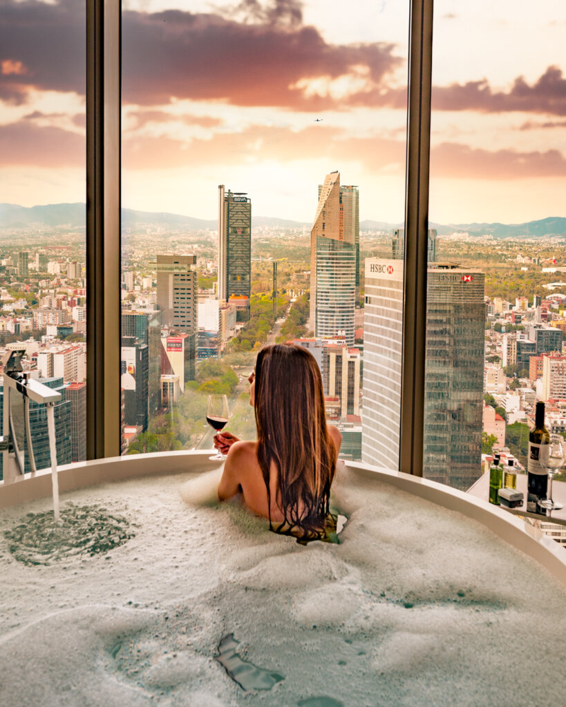 girl sitting in a bathtub and overlooking Mexico City