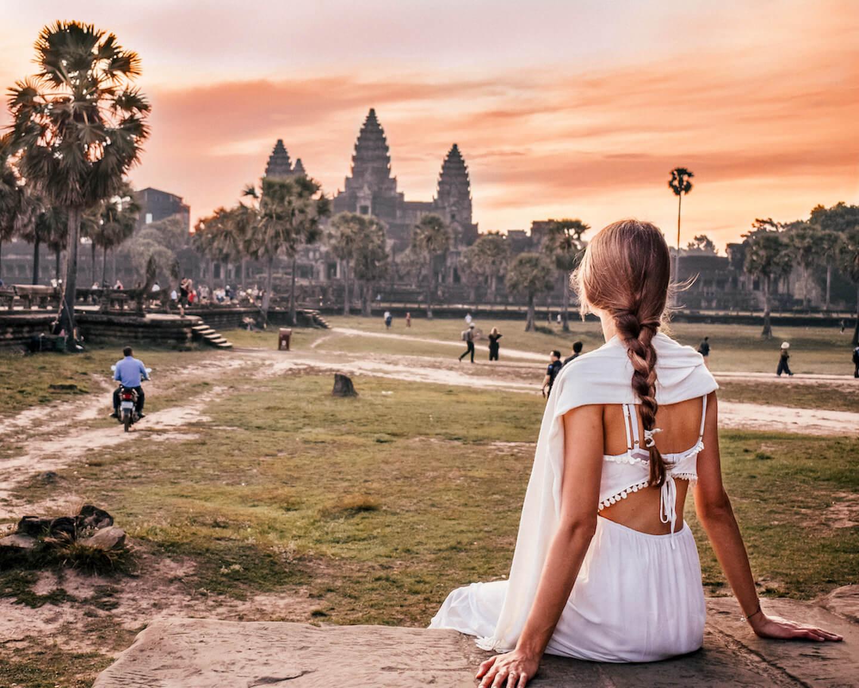 girl watching sunrise behind Angkor Wat temple