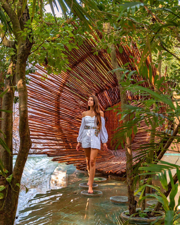 girl walking through wooden gate at azulik hotel in Tulum