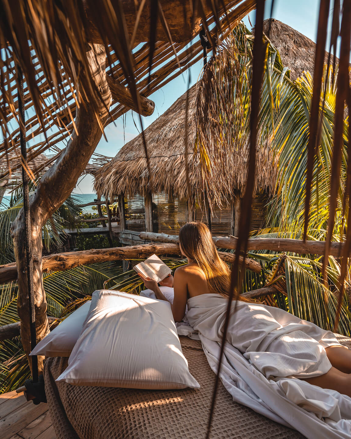 girl laying on mattress in the jungle reading a book and watching the ocean in Tulum