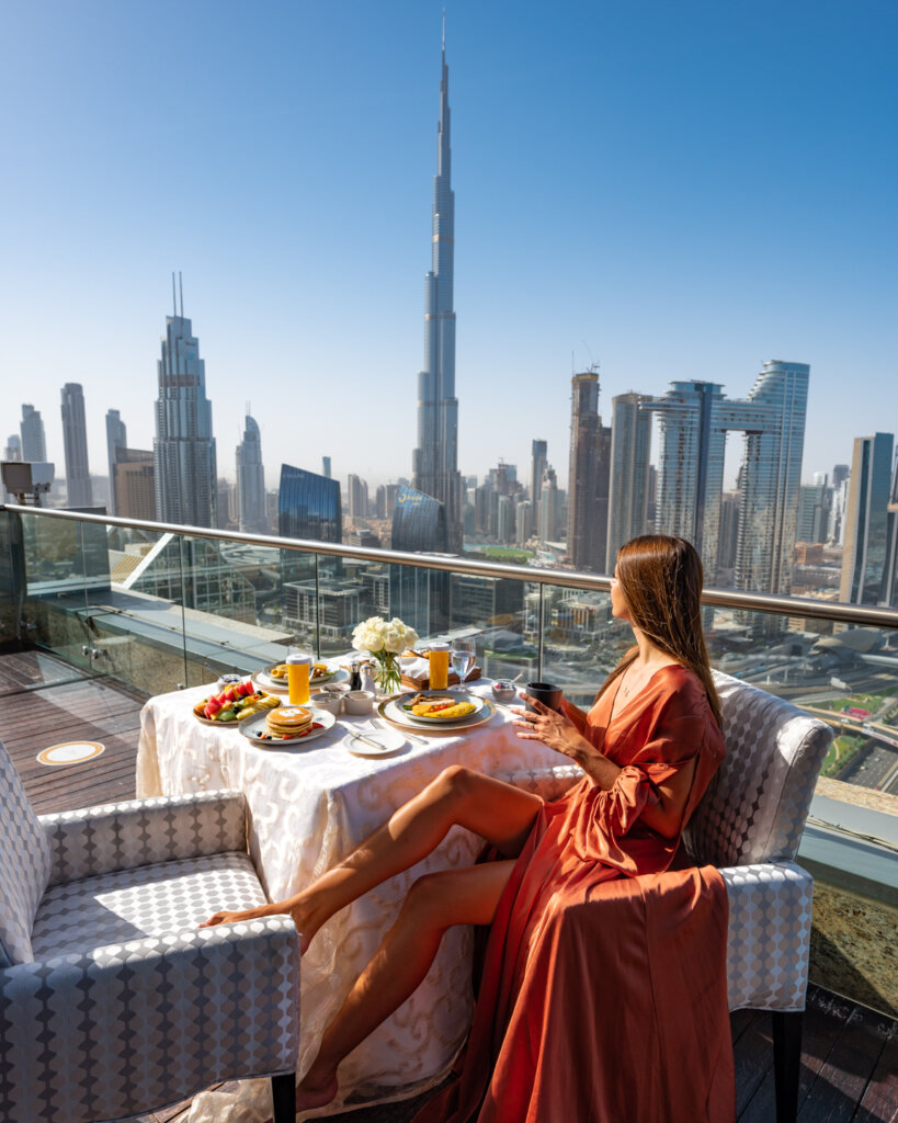 girl sitting at the terrace of the Shangri-la dubai with breakfast setup and overlooking the Burj Khalifa