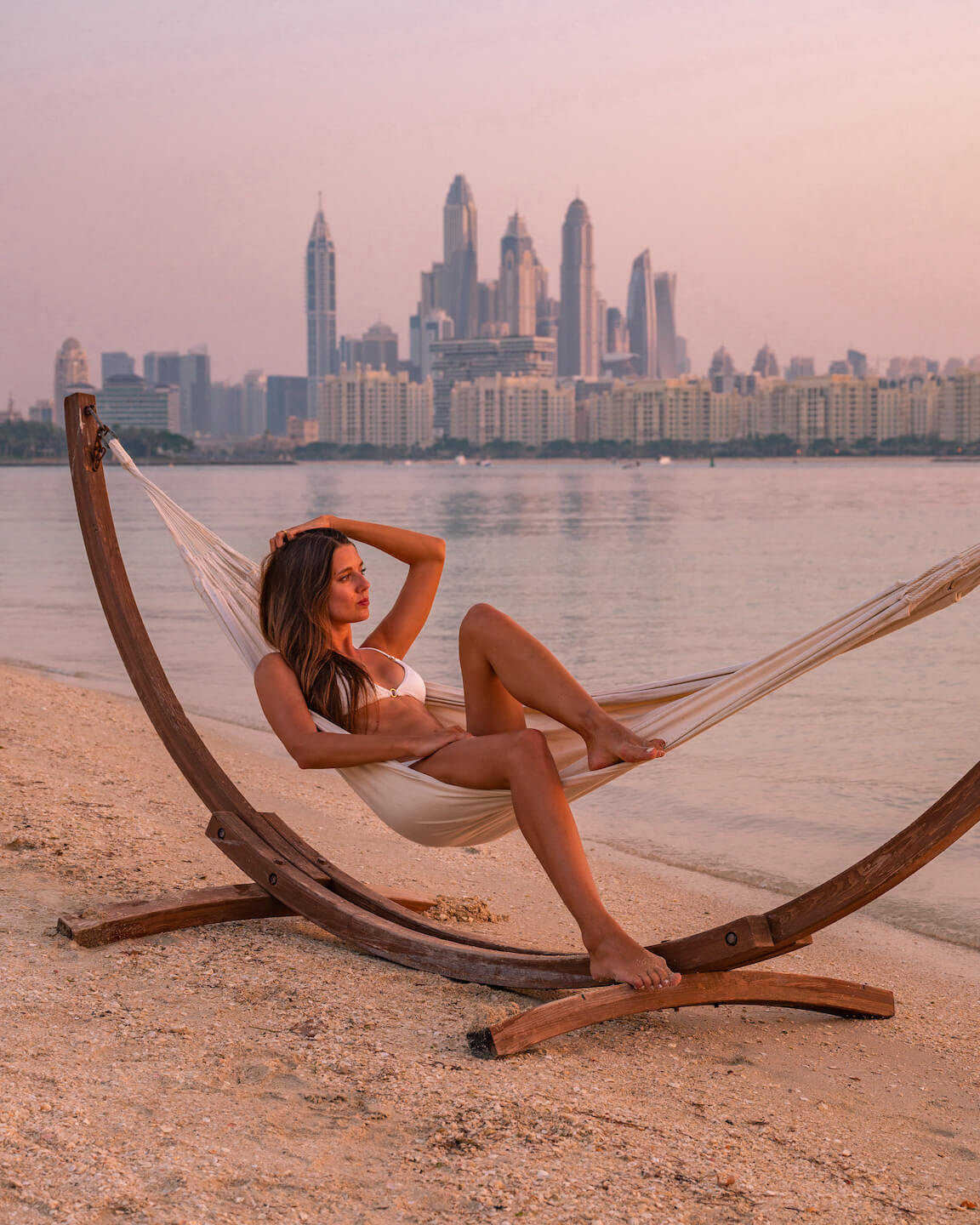girl sitting in hammock with view of Dubai Marina in the background