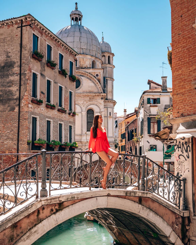 girl sitting on a bridge in venice