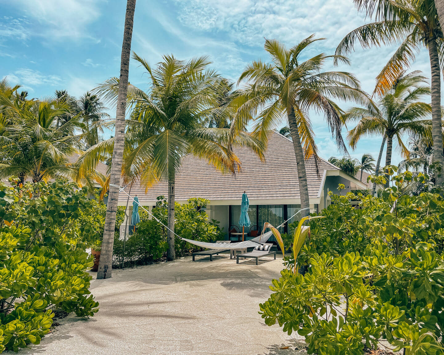 Beach Villa of the SAii Lagoon Maldives Hotel surrounded by palm trees with a hammock