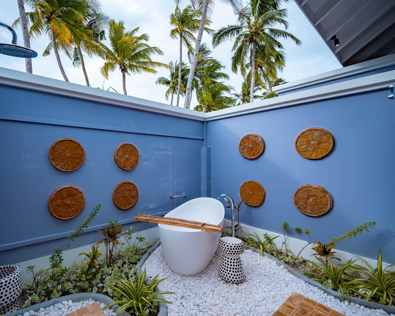 outdoor bathroom of a beach villa at the SAii Lagoon Maldives with a freestanding bathtub