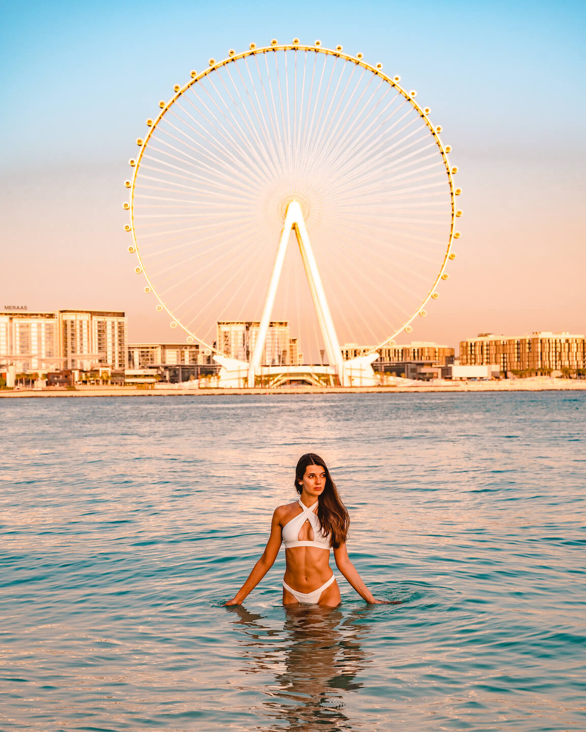 sunrise at the beach with a view at the Ferris wheel in dubai
