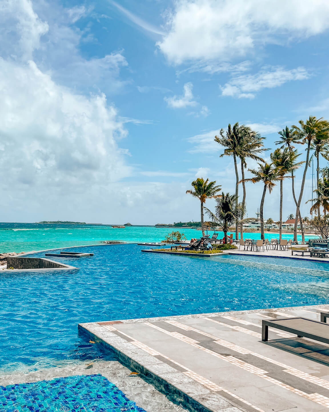 main pool with ocean view and palm trees at the SAii Lagoon hotel Maldives
