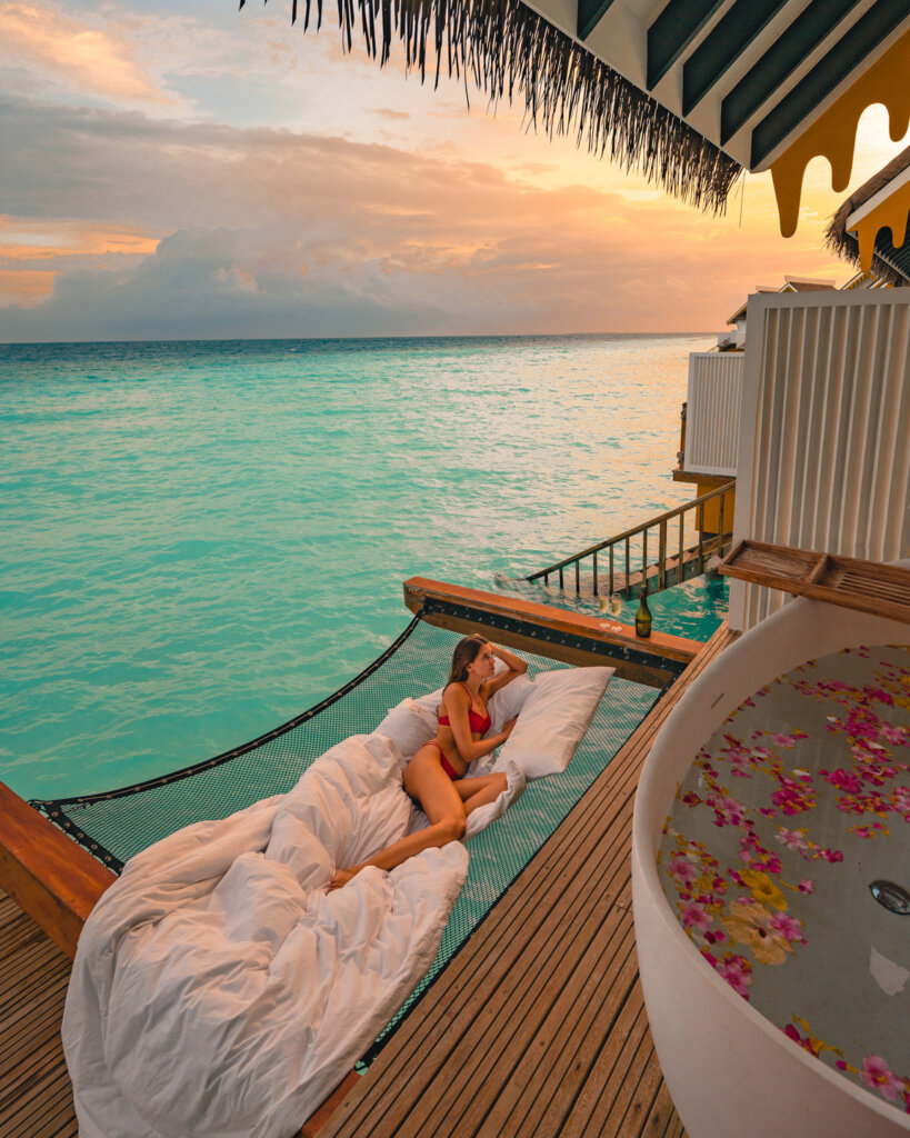 girl sitting in a hammock with pillows next to a bath tub with flowers on the terrace of a water villa in The Maldives and watching the sunset