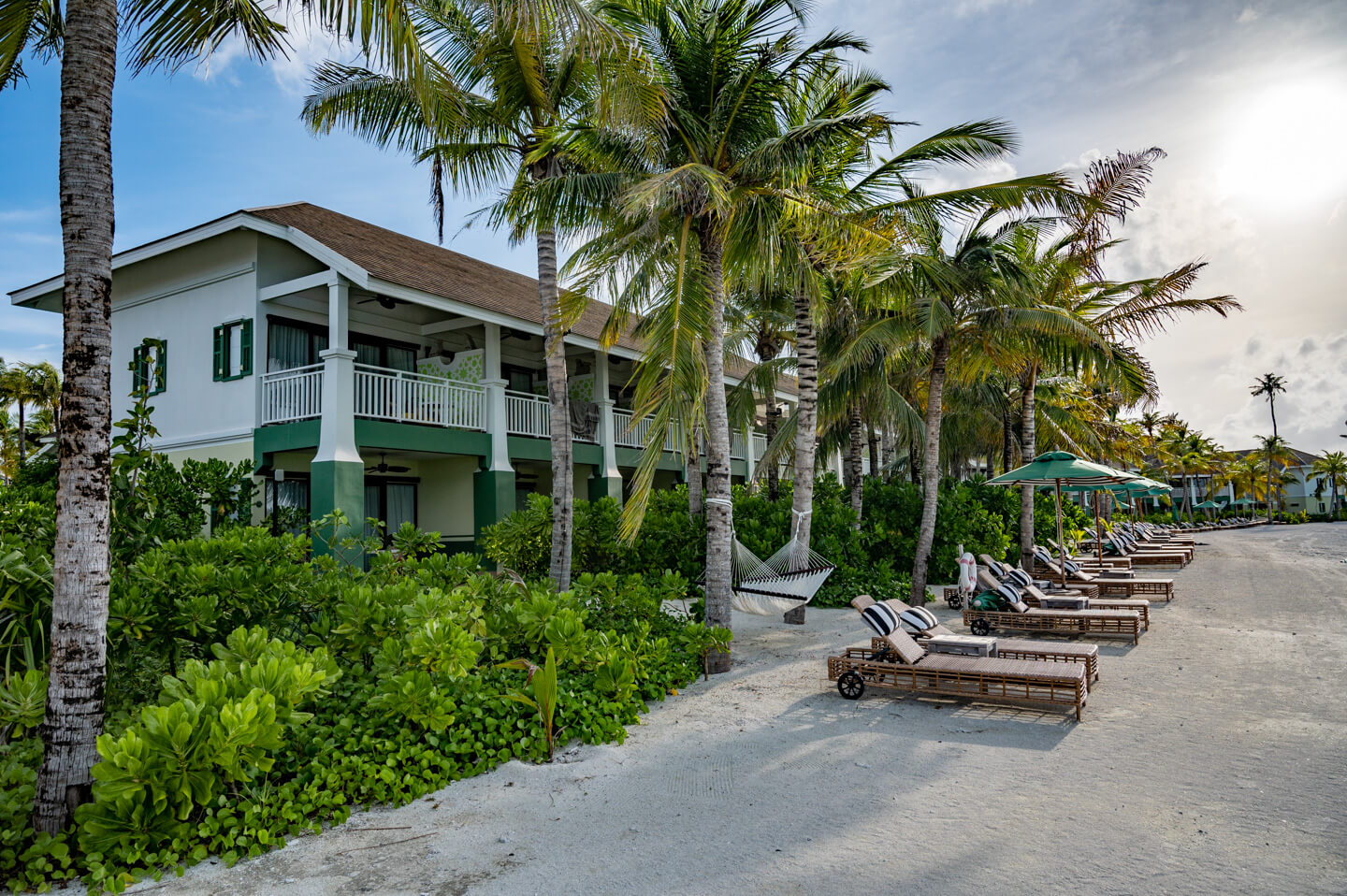 house at the beach with sun beds and many palm trees in The Maldives, SAii Lagoon