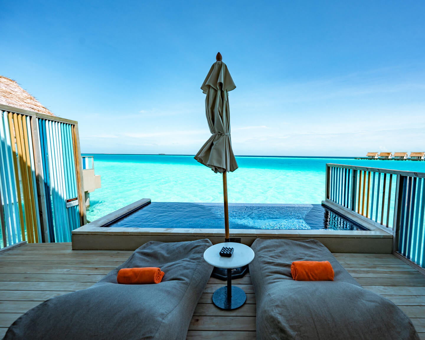 terrace with sunbeams and pool overlooking the blue lagoon at the hard rock hotel maldives