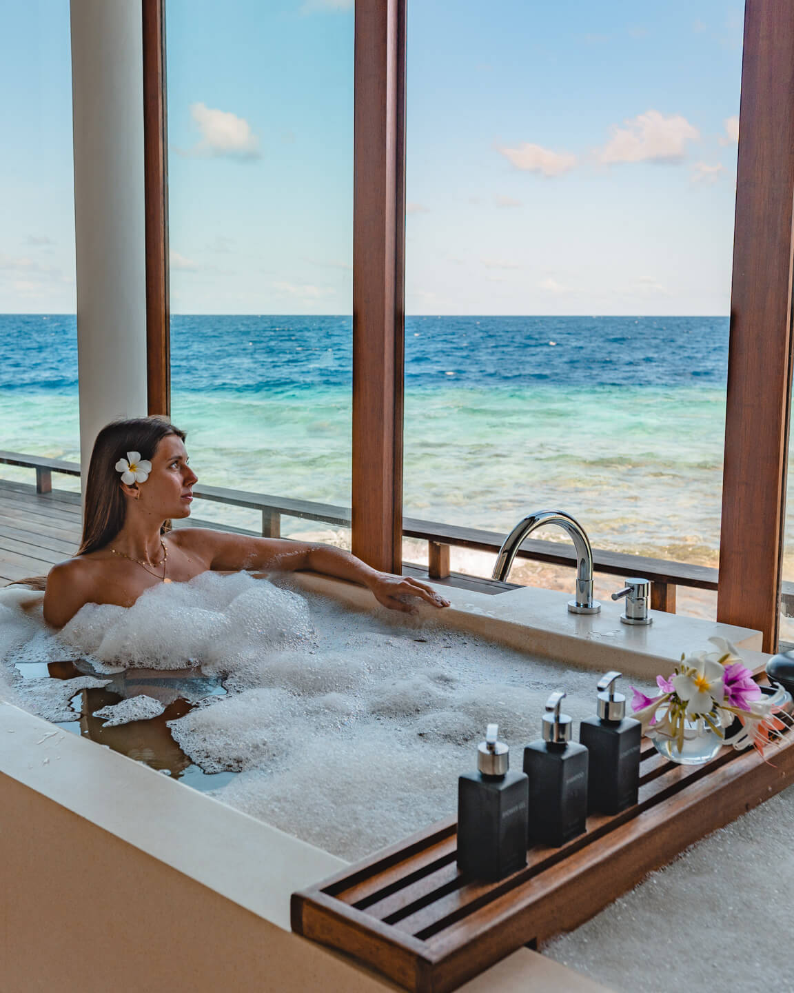 girl sitting in a bathtub in a water villa overlooking the blue lagoon in the maldives