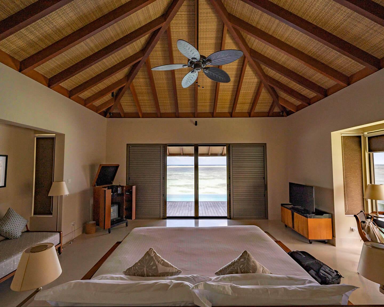 bedroom of a water villa at the residence maldives dhigurah