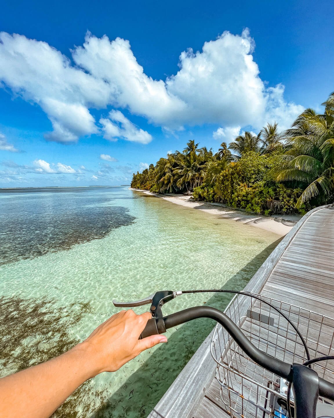 bicylce ride over the jetty in the maldives with island view in the background