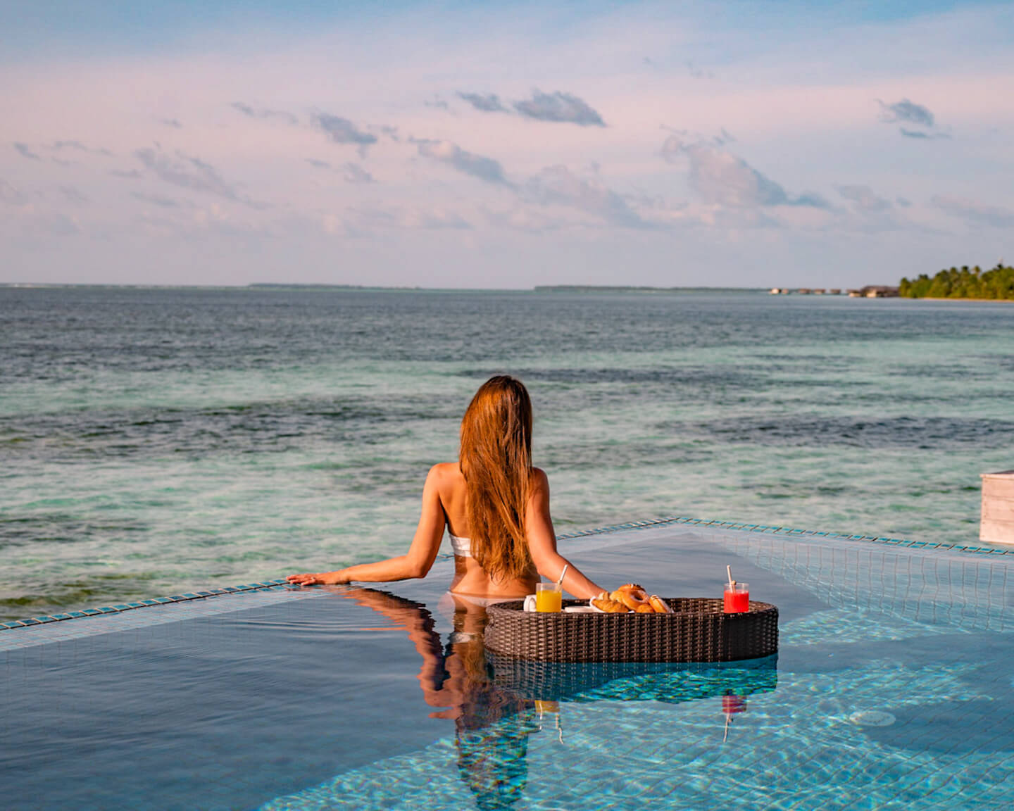 Floating breakfast in infinity pool over the blue lagoon in The Maldives
