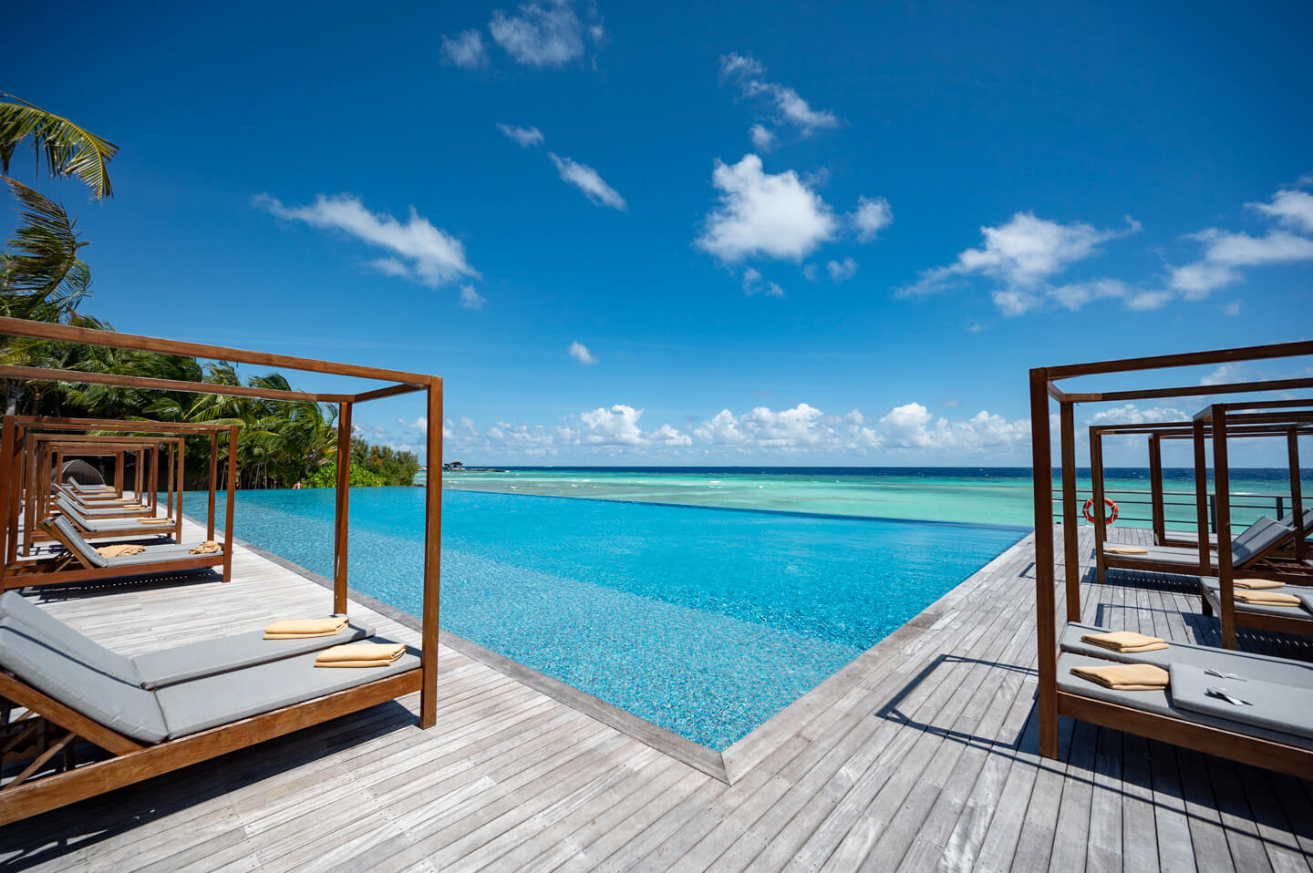 main pool with sun beds and ocean view at the residence maldives dhigurah