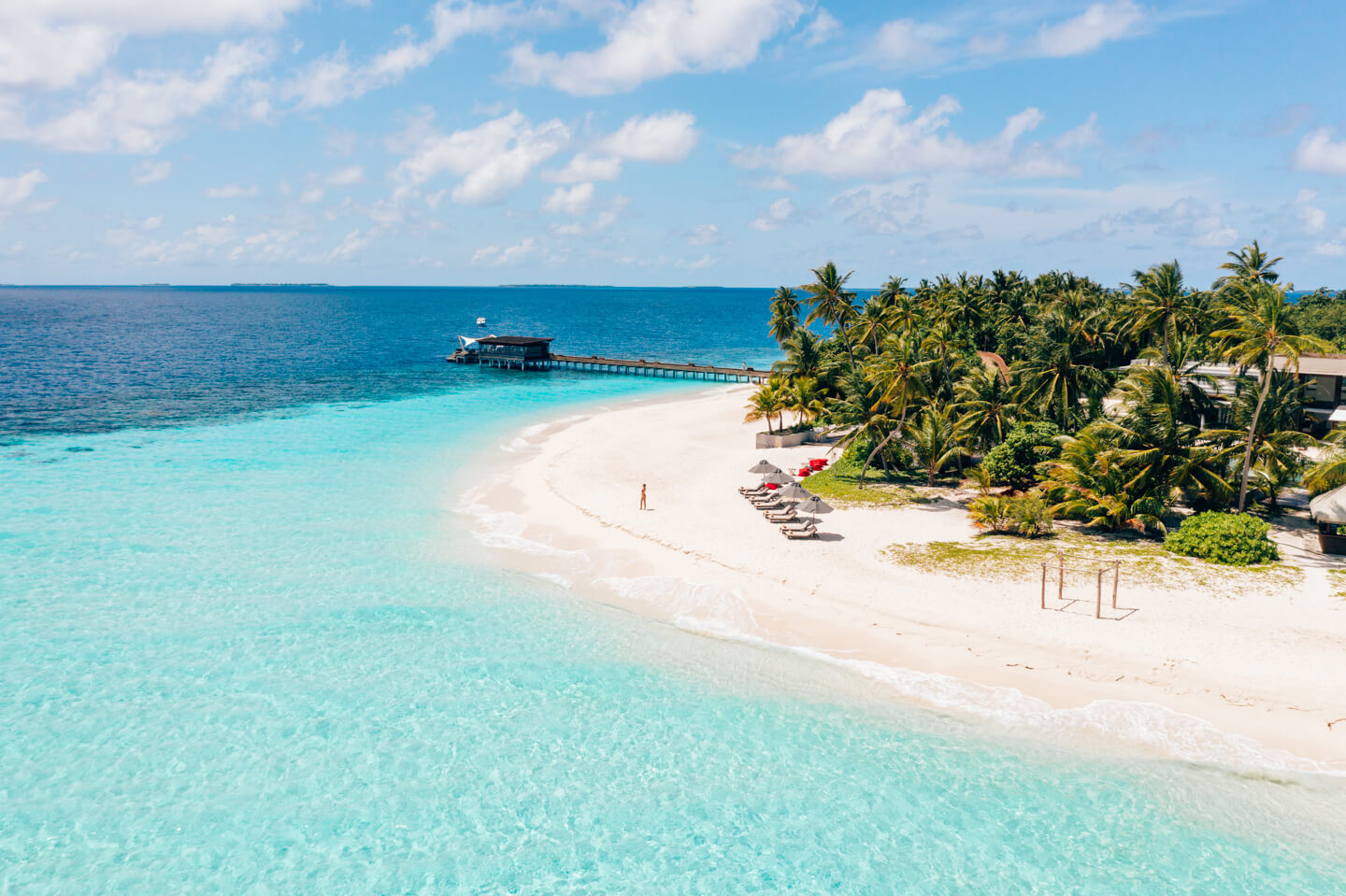 maldoves drone shot with a blue lagoon, white sandy beach and many palm trees