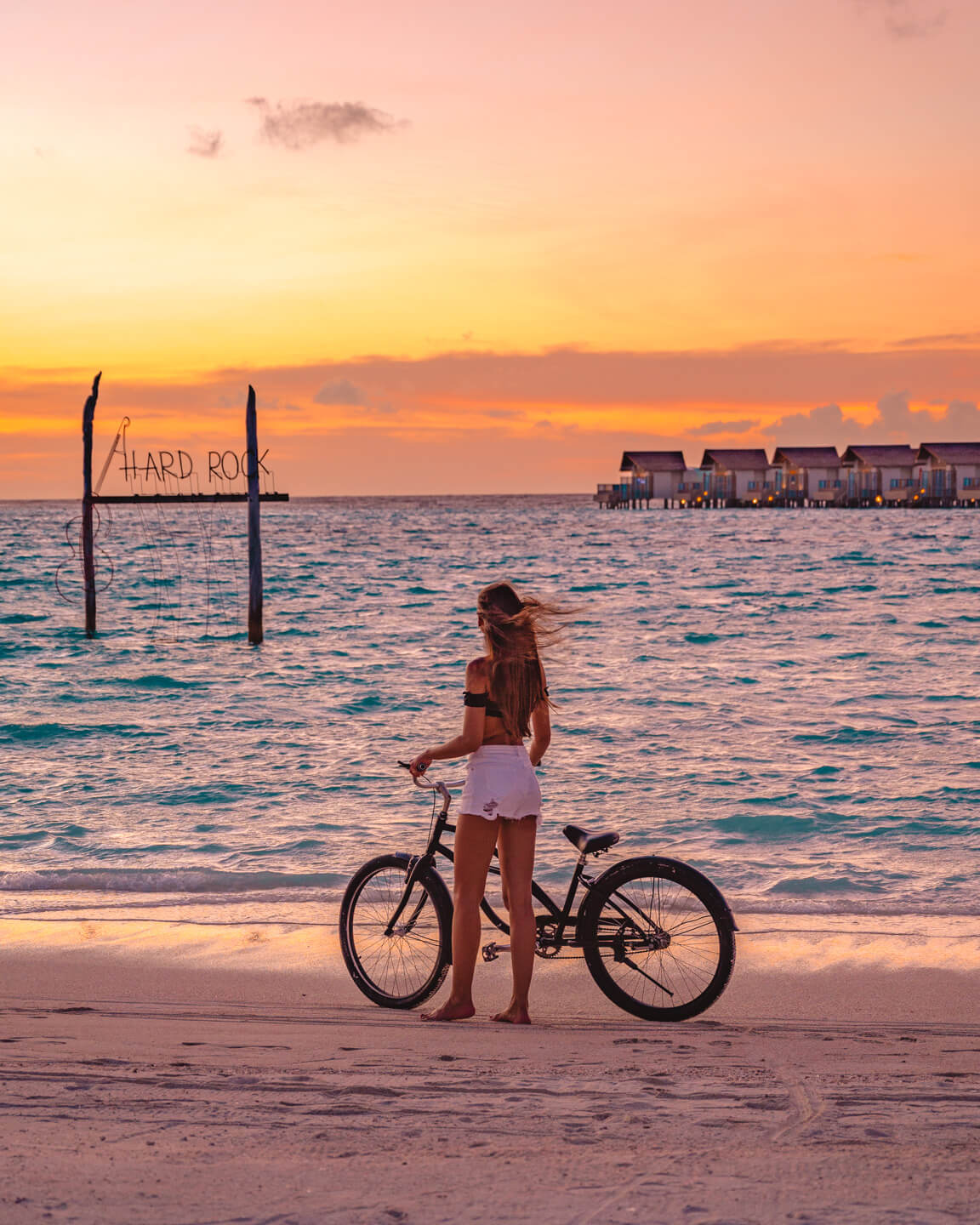 girl standing at the beach with a bicycle while watching the sunset in The Maldives