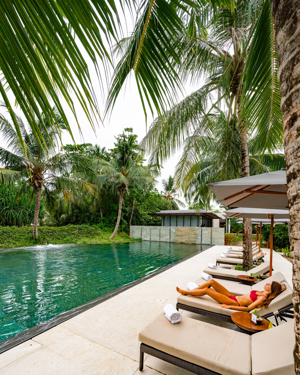 girl relaxing at a pool in The Maldives surrounded by palm trees