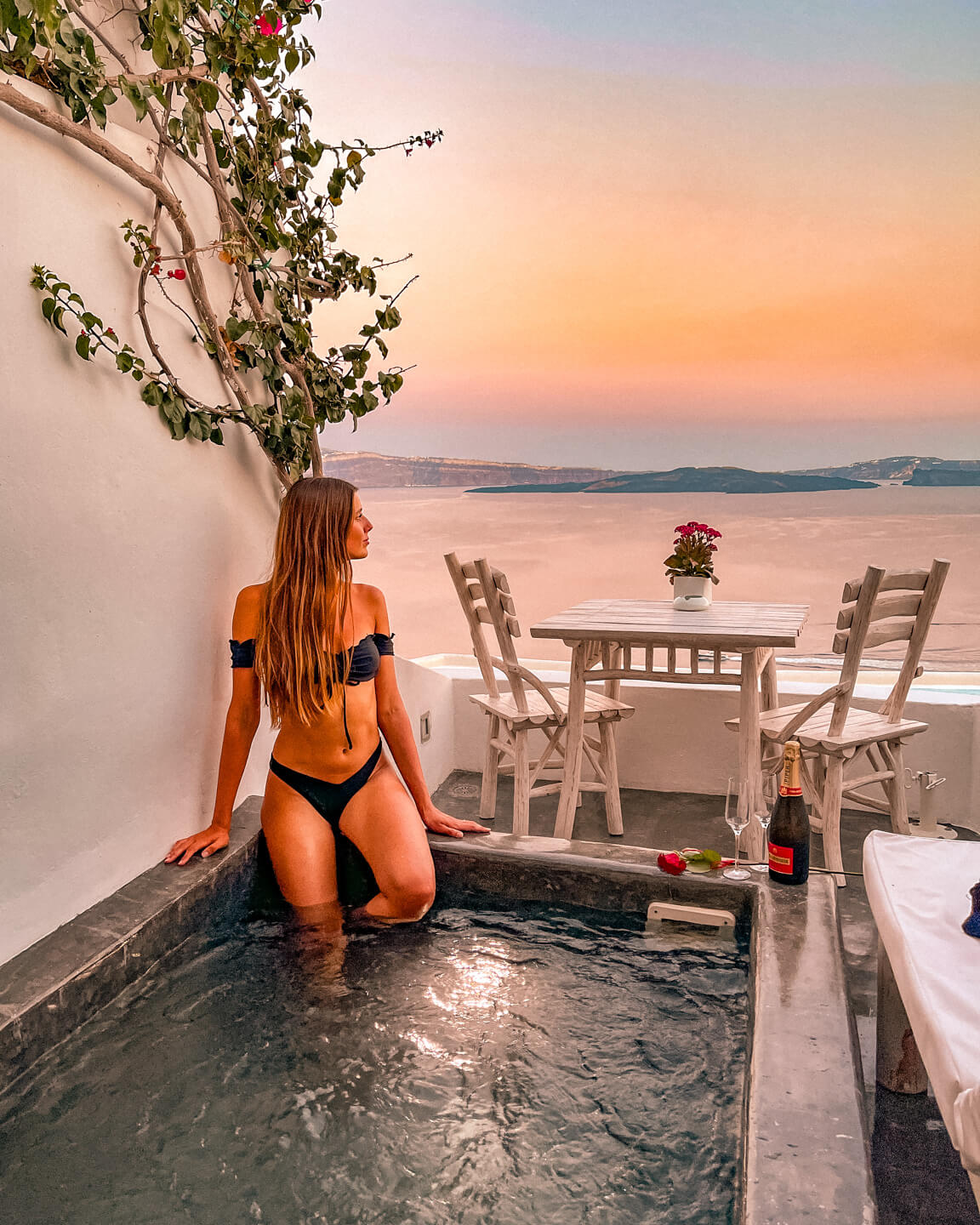 sunset view from private jacuzzi in suite in santorini, greece